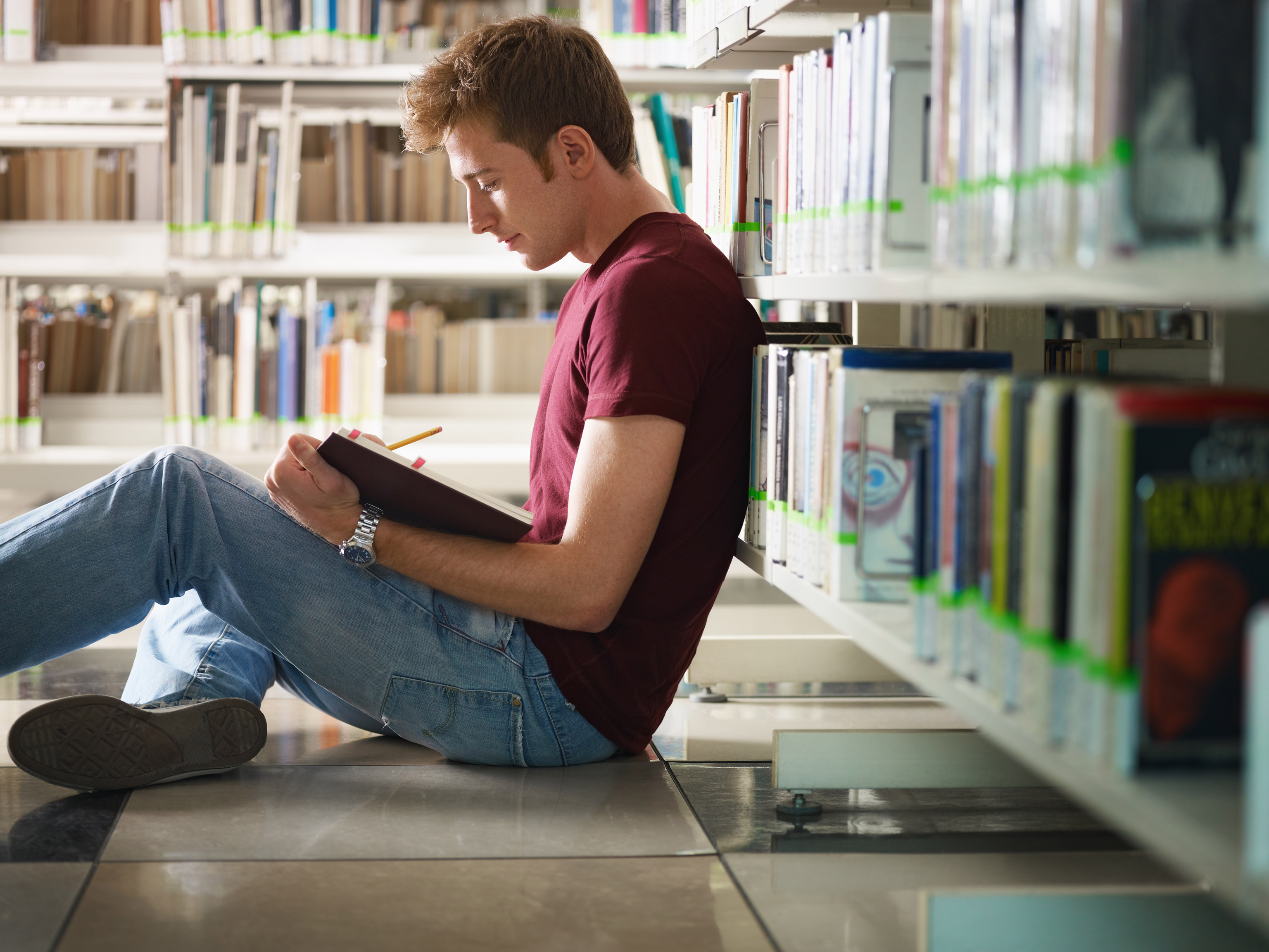 College student sitting on floor in library and reading