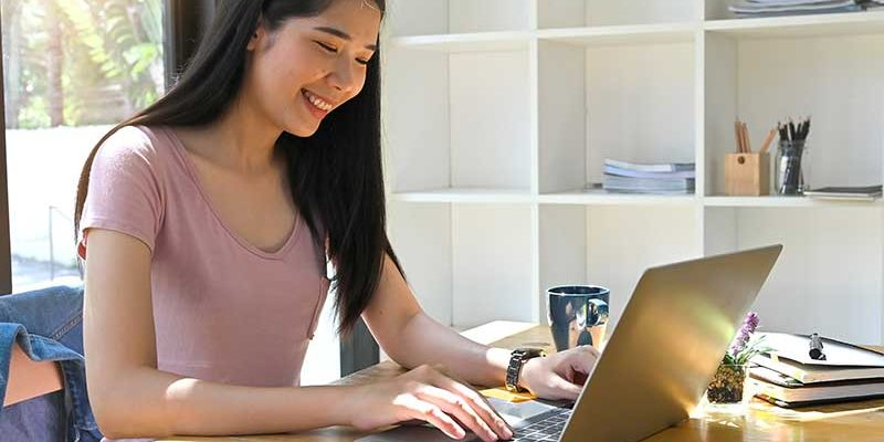 Student formatting scholarship essay on her laptop
