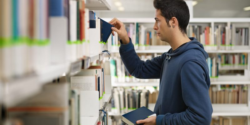 College student in library researching for scholarships