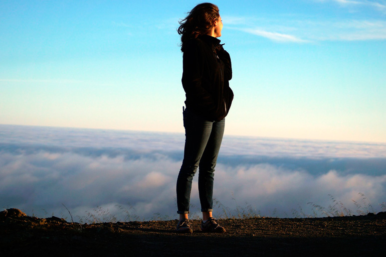 Lady standing on top of a mountain